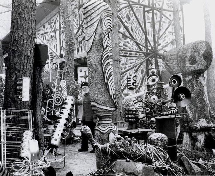 """L'homme des bois    """"Je suis riche de pauvreté, ils sont pauvres de richesses.""""  En 1960, amer et virant total mystique, Chomo s'exile à Achères-la-Forêt, où, pendant quarante ans, il se fabrique loin du monde et du confort un univers imaginaire peuplé de créatures souffrantes et étrangement asexuées : le Village d'Art Préludien.  / Photo : DR  / Halle Saint-Pierre"""