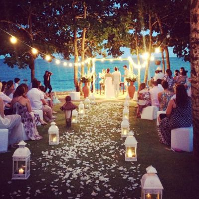 Wedding ceremony outside, at dusk, on the water. Hanging lights and lanterns. Breathtaking.