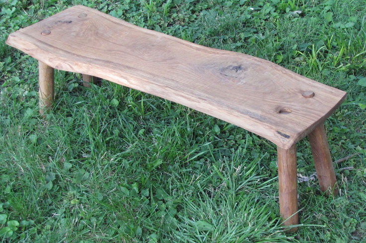 A bench made from oak and not trimmed to a straight edge.