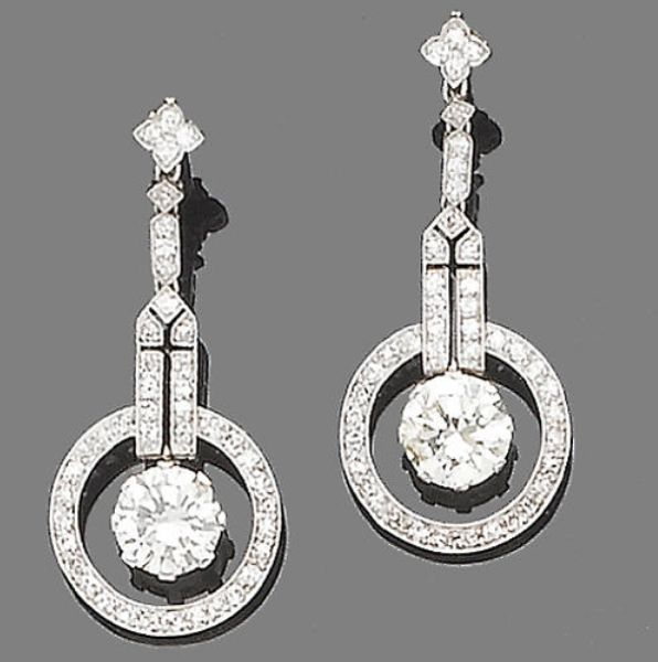An pair of Art Deco diamond pendent earrings  Of geometric design, each brilliant-cut diamond suspended within an openwork single-cut diamond halo and pierced geometric surmount, to an articulated similarly-cut diamond surmount, principal diamonds approx. 2.80ct. total, remaining diamonds approx. 0.85ct. total, length 3.8cm.
