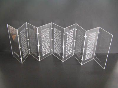 Artist Helen Malone Title The Illuminated Book of Babel Year 2007 Medium Concertina book Height 20 cm Width 10 cm Depth 3 cm Engraved perspex book containing seven different visual languages unable to be read or understood.