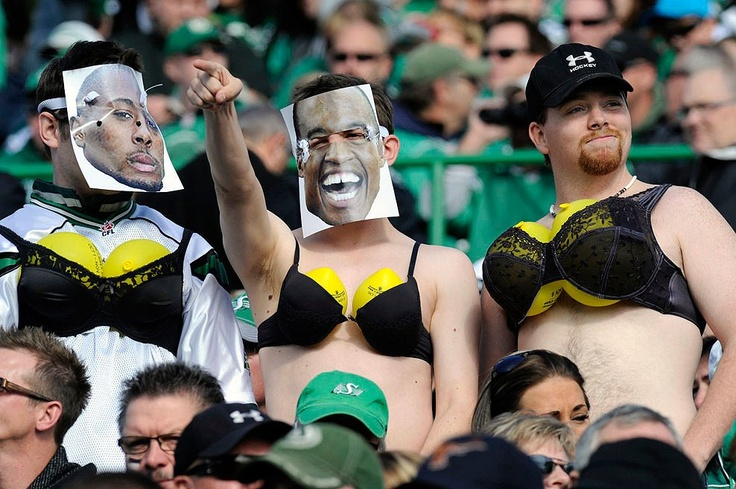 Homens usam máscaras com fotografias de jogadores e sutiãs durante jogo da liga de futebol canadense. Canadá, 17 de outubro de 2010.