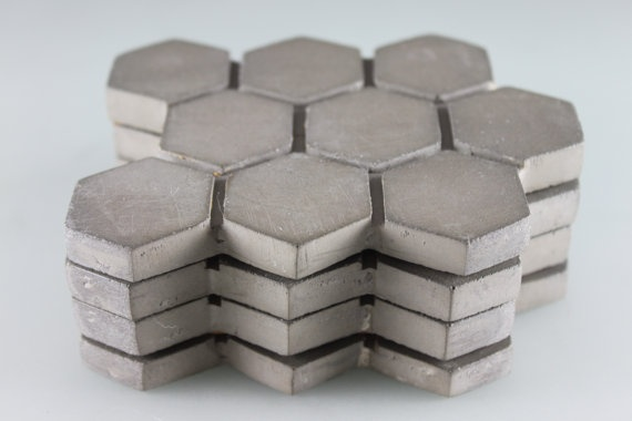 Awesome concrete coasters from CULINARIUM on Etsy.  http://www.etsy.com/listing/76252747/concrete-hexagon-coasters-large