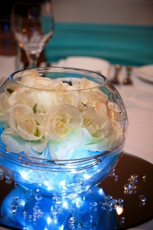 Table centrepiece. Soljans fish bowl, cream roses, silver wire, blue lights, diamantes on round mirror.