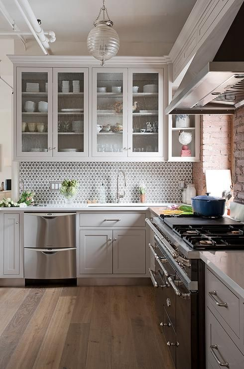 Seeded glass kitchen cabinets are mounted beside a display shelf and above light gray shaker cabinets fitted with polished nickel pulls and a stainless steel stacked dishwasher fixed beneath a white quartz countertop lined with silver and gray mosaic backsplash tiles.
