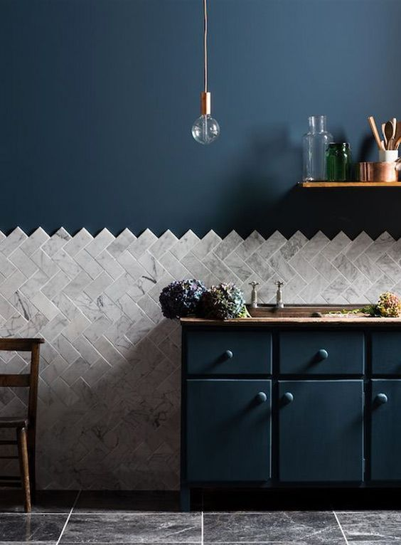 Beautiful marble subway tile.  This kitchen uses chevron pattern to accent the white marble again royal blue walls.