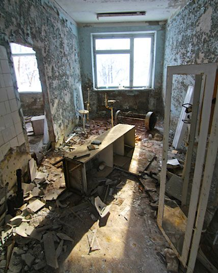 An abandoned medical examination room in the hospital, littered with medical instruments
