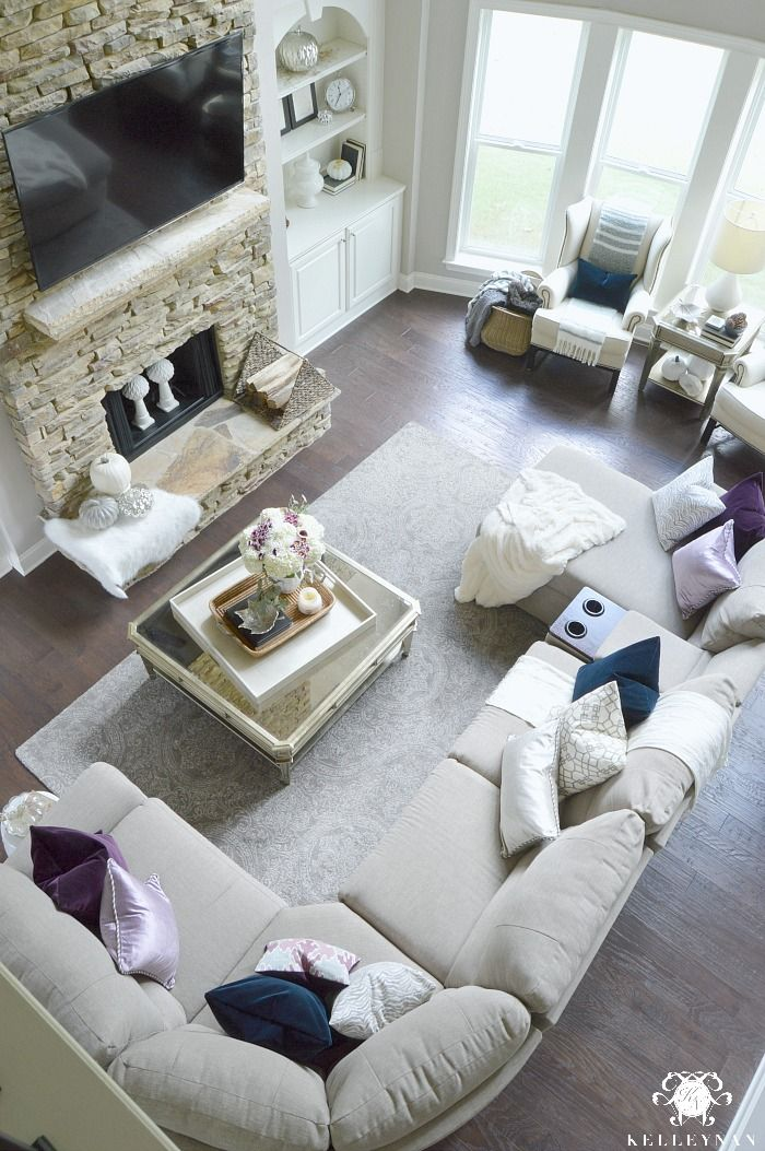 Two Story great room with gray sectional decorated for fall in plum, navy, and lavender. A stacked stone fireplace is the room's focal point.