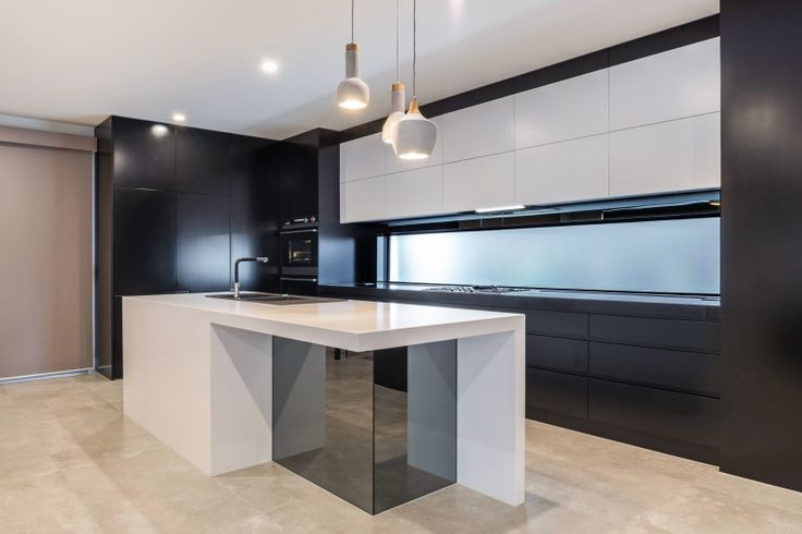 Stunning modern black and white kitchen with stone tops and mirror splashback