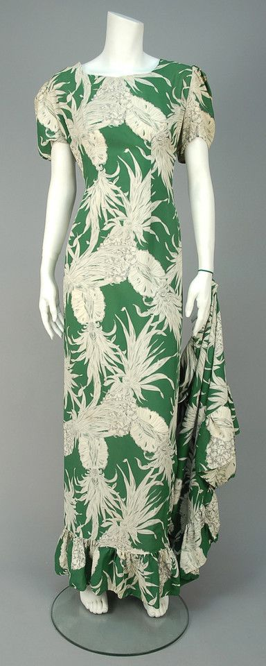 TRAINED HAWAIIAN LABEL GOWN, 1940s. Green rayon with grey and white pineapple print having short sleeve gathered at shoulder, trumpet flared skirt with hem ruffle and long train and finger loop for dancing. Honolulu label. - whitakerauction