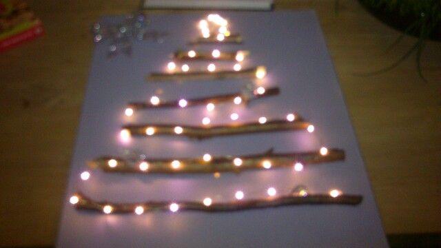 Kerstboom van takken en lampjes op schilderdoek