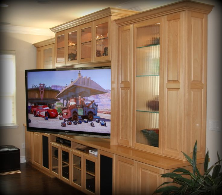 A custom media cabinet with storage for video game consoles, a built-in home bar & an adjustable TV mount are just a few Bay Area entertainment room essentials.