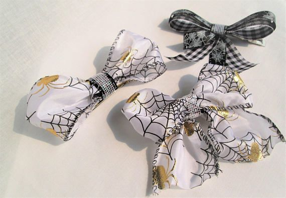 """These bows, made from spider themed ribbons, look spooktacular for costumes, photo shoots, and even everyday use! They stay nicely in hair with alligator style, metal clips. For children and adults, these cute bows make a great accessory that is comfortable for all day wear. White w/ tails: 4x3.5"""" Black bow: 4.5x3.5"""" White w/o tails: 2x6""""  All bows mounted onto metal alligator clips that are approx. 3"""" long Made from a variety of ribbons White ribbon is wired for personal shaping   ..."""