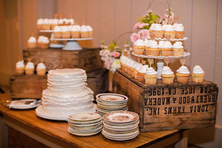 farm table holds wedding cake and cupcakes