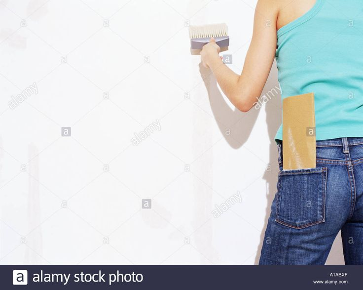 Download this stock image: Woman painting a wall - A1ABXF from Alamy's library of millions of high resolution stock photos, illustrations and vectors.