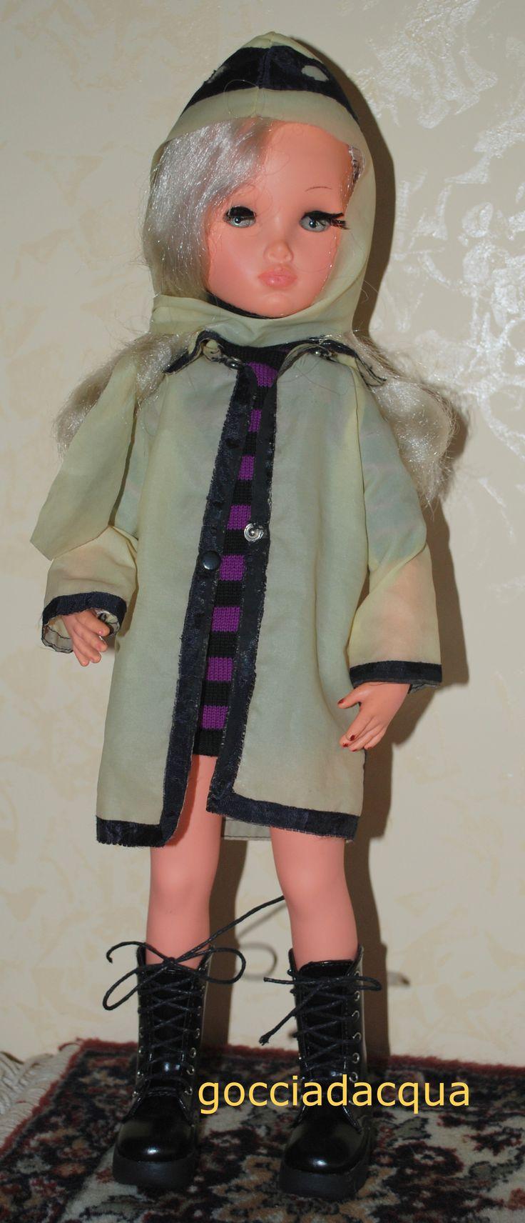 Sylvie con l'impermeabile 'Sotto la pioggia' (originale) del 1967, indossato su un miniabito di maglia a righe ed abbinato ad anfibi neri