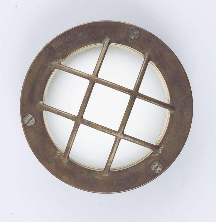 Marina Faretto con Griglia Parete/Soffitto Diam. 14cm  Lampada da Esterno sia per parete che per soffitto in fusione di ottone anticato e vetro bianco satinato con griglia. Diametro di 14 centimetri ed un grado di protezione IP55.