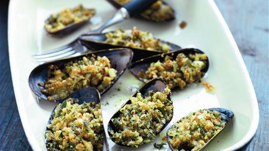 Blanda ost med schalottenlök, vitlök, persilja, ströbröd, svartpeppar och olivolja. Fördela blandningen över varje mussla. Gratinera i ugn 225 grader tills osten smält, ca 10 minuter. Tag ut musslorna och låt dem svalna i några minuter. Servera som förrätt, drinktilltugg eller snacks.