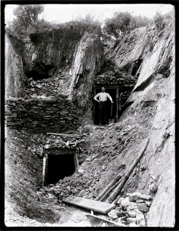 California Gold Rush. Entrances to two mine shafts; man with shovel standing at one of the entrances |