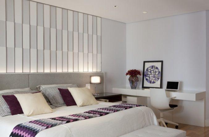 Quarto com cabeceira de tecido cinza claro + parede com painel branco geométrico + iluminação de destaque. Projeto Marcelo Rosset.