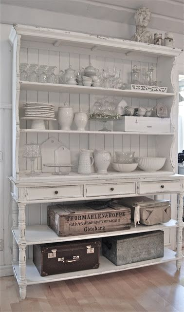 WHITE WOODEN SHELVES WITH VINTAGE SUITCASES AND WHITE CERAMIC POTTERY