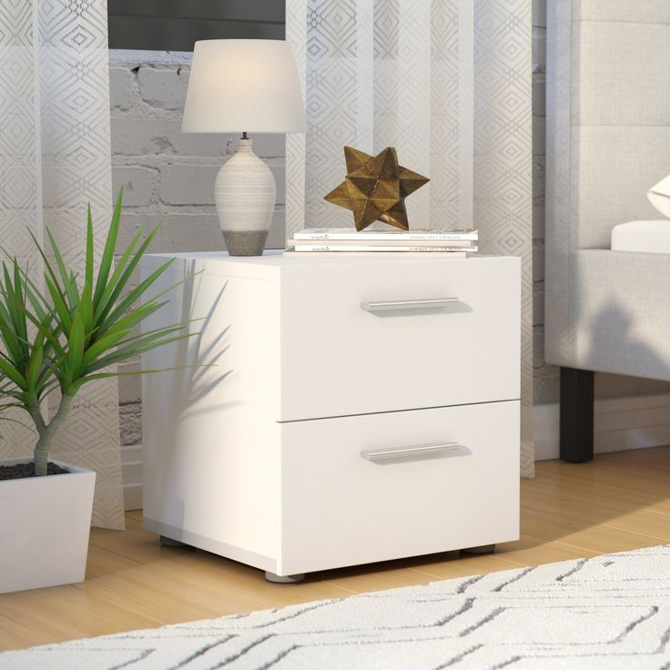 Inspired by Scandinavian design, minimal details and a clean-lined silhouette define this two-drawer nightstand. Made from practical manufactured wood with laminate veneers, this piece features sleek bar pulls and round plastic feet. To create a contemporary ensemble in your master bedroom, start by rolling out an overdyed area rug in the middle of the floor, then place one of these nightstands on each side of a low-profile platform bed. Illuminate the room in eclectic style by placing a…