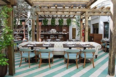 """Striped tile floor makes this space.  Cecconi's may be the most beautiful restaurant in Miami.  """"Designer Martin Brudnizki created a gorgeous oasis underneath Silver Buttonwood trees and bell jar hanging light fixtures.  The trees are also wrapped in white lights and the effect at night is magical.   I especially love the tile Antique Nile green floor tiles that are set on an angle that seem to lead you through the space.  The extra long tufted Chesterfield sofas are also a chic nod to the…"""