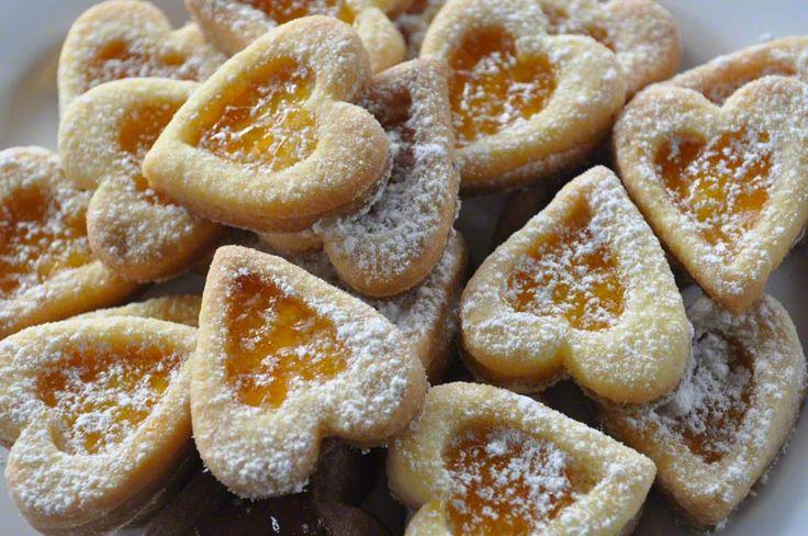 FROLLINI A FORMA DI CUORE Biscotti di pasta frolla ripieni di marmellata di albicocche e spolverizzati con lo zucchero a velo.