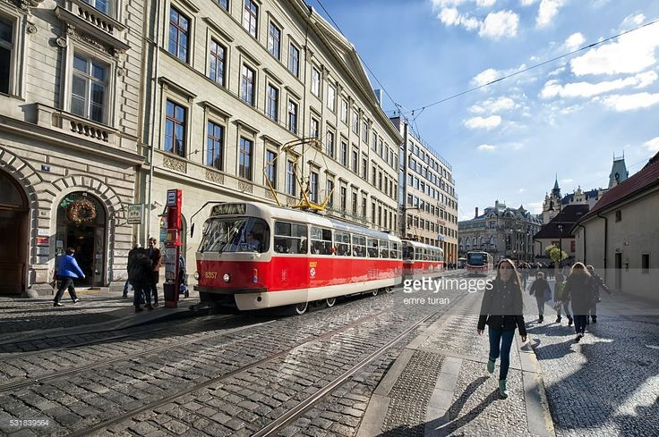 sunny afternoon view of na porici Street with red tram passing in prague
