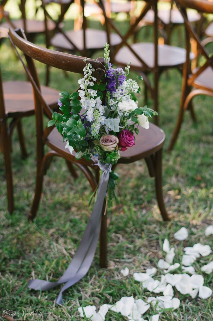 pew marker of lavender delphinium, purple larkspur, lavender roses, purple roses,dusty miller, seeded eucalyptus and white spray roses  is tied to the french country chair with grey satin ribbon.