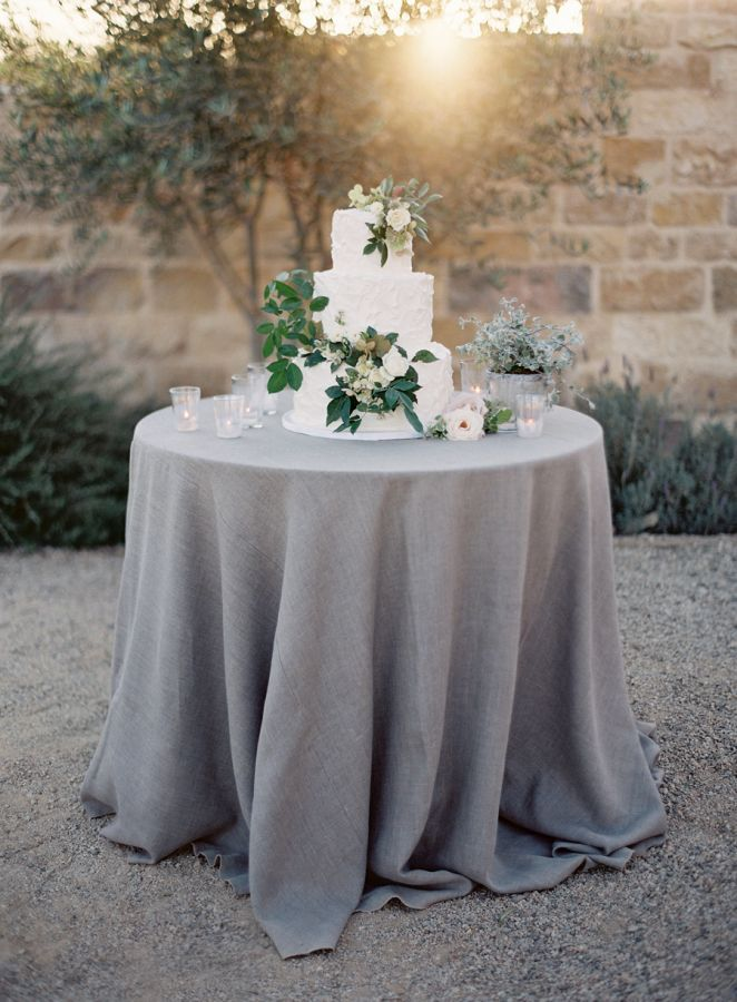 simple white three tier wedding cake with floral accents displayed on a grey linen draped round table | Intimate Sunstone Vineyards Wedding