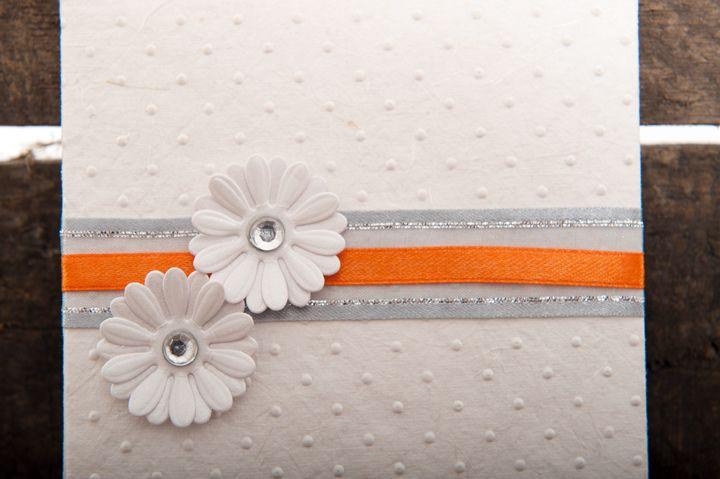 Pretty white wedding invitation with orange satin ribbon detail with two white daisies with diamante centers.