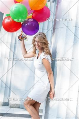 Kobieta w bieli z kolorowymi balonami. Moda z InteractiveStock.
