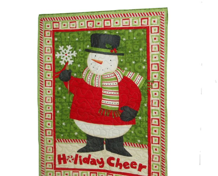 "Snowman Wallhanging - Quilted - Holiday Cheer   •100% Cotton Fabric   •Smiling Snowman   •Holiday Cheer   •Special sewn area on back for easy hanging     This seasonal wall hanging is machine quilted with 100% Cotton Fabric. It measures 21 X 27.5"". It has layer of cotton batting and the back is green holiday cotton fabric. Has a special sewn area on back to insert dowel for hanging. It makes a great winter decoration and will give you several months of enjoyment looking super on any wall!!"