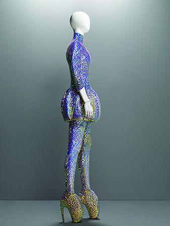 "* Alexander McQueen (British, 1969–2010). ""Jellyfish"" Ensemble Plato's Atlantis, spring/summer 2010. Dress, leggings, and ""Armadillo"" boots embroidered with iridescent enamel paillettes. Photo Sølve Sundsbø"