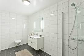 Grått gulv og hvite fliser på veggen. Do, vask og dusjhjørne med 80x80 dører som svinges bort når den ikke er i bruk.