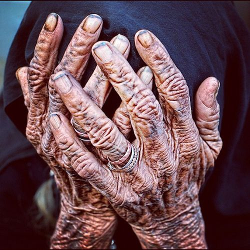 Old hands. Extremely wrinkled. Discoloration of skin in darker shades like they have been worked for a long time. Could also be dirt. Dirt in the nail beds.