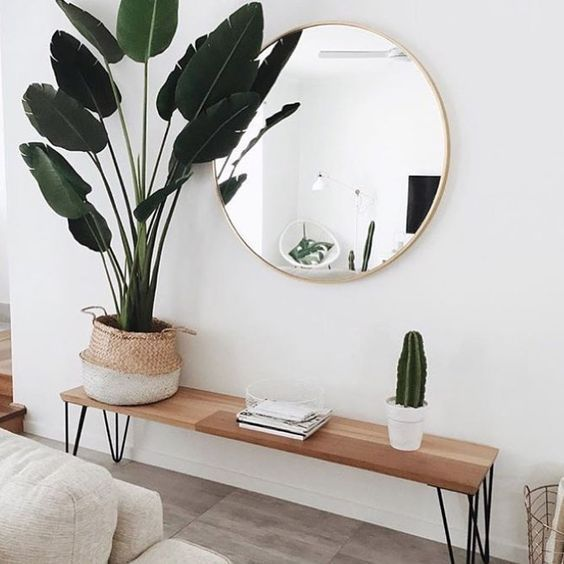 Skandinavisches Wohnzimmer. Eine Bank aus Holz, ein Spiegel mit Golddetails und …