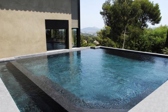 Pour cette petite piscine à débordement, le bac tampon est enterré.