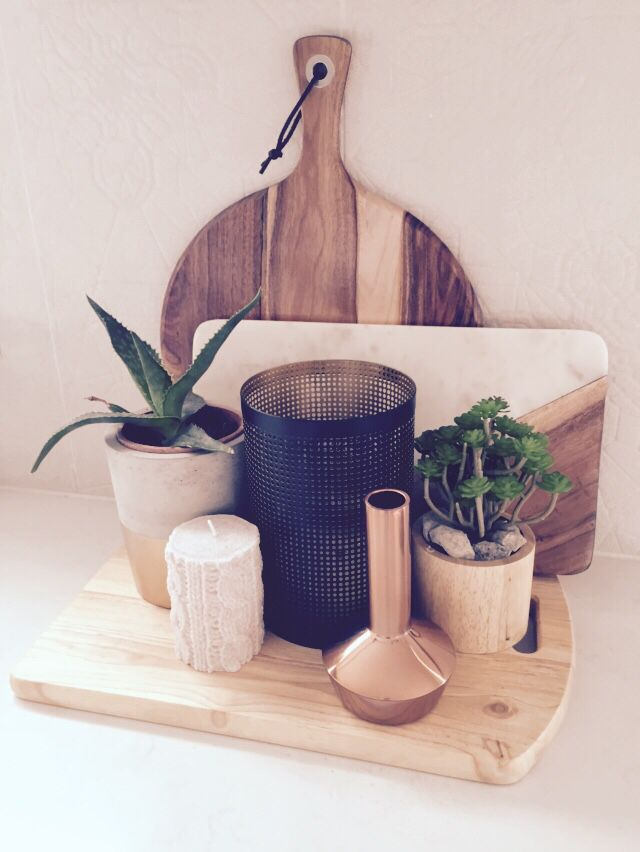 Kitchen styling using timber and marble chopping boards, aloe vera plant and a variety of candles.