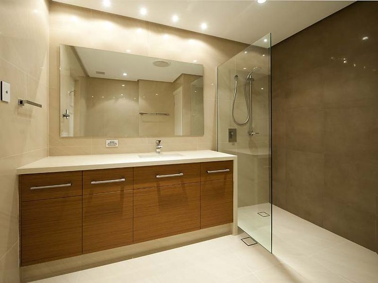 We love the tiles, timber look vanity doors and waterfall end. We don't like the incorrect placement of the room drain and the shower waste, they should have used a gully drain at the back of the shower for good drainage.