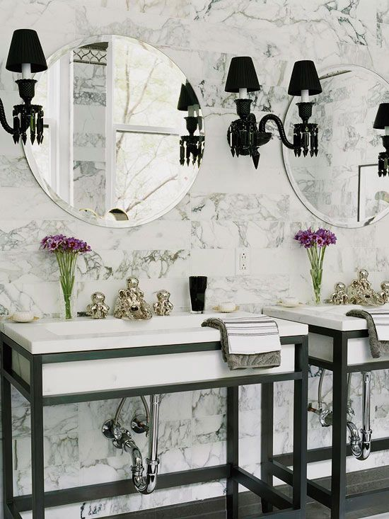 Bathroom Vanity with Cool Contrasts  Add a modern element to your bathroom by using black on the sconces and vanity. In this bathroom, two rectangular marble sinks are encased by lacquered black metal frames, offering a contemporary twist on the old-fashioned washstand. Black Baccarat sconces drip with glamour, while exposed pipes and octopus-shape faucets shine in silvery metal. White Italian marble offers a classic backdrop behind the eye-catching vanity.