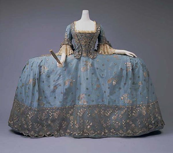Court dress (image 7) | British | 1750 | silk, metallic thread | Metropolitan Museum of Art | Accession Number: C.I.65.13.1a–c | In its most formal configuration, the robe à la française presented a particularly wide and flattened profile accomplished by enlarged panniers. Constructed of supple bent wands of willow or whalebone and covered in linen, panniers took on broader or narrower silhouettes.