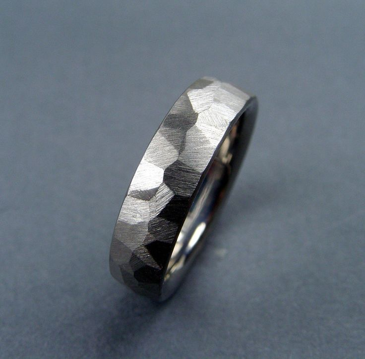 This titanium ring has facets cut into it, making no two the same, giving it an asymmetrical organic texture that resembles rocky cliffs. Each one is cut by hand and truly one of a kind. Ring will arr