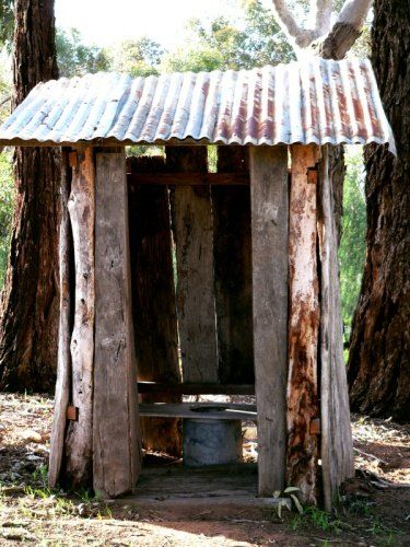 Outhouse -- Aussie Dunny with walls of bush timber, corrugated iron roof, and galvanised pan.