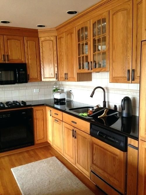 Honey Oak Cabinets With Black Countertop And Black Hardware