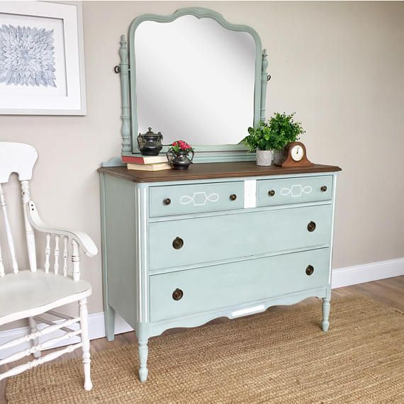 Add a wonderful nostalgic flair to your space with this antique dresser from the 1930s. A 4 drawer dresser that offers lots of storage space for hair and makeup necessities. The soft blue/green color adds a subtle pop of color to your farmhouse, country or beach interior. Built sturdy and strong with old fashioned craftsmanship to last another lifetime. • Very Sturdy and built strong • Farmhouse Style • Well Functioning Drawers  44 W x 20 D x 35 H  66 H {to the top of the mirror}  It has...