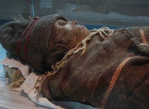 """Una de las momias más famosas del Tarim Basin es el cuerpo de una joven conocida como """"La Bella de Loulan"""". Vestida con un gorro de fieltro y traje de colores, su cara de altos pómulos es claramente caucásica. Su rostro está tan bien conservado que se pueden ver sus largas pestañas. Fue enterrada junto a una canasta de grano bellamente tejida."""