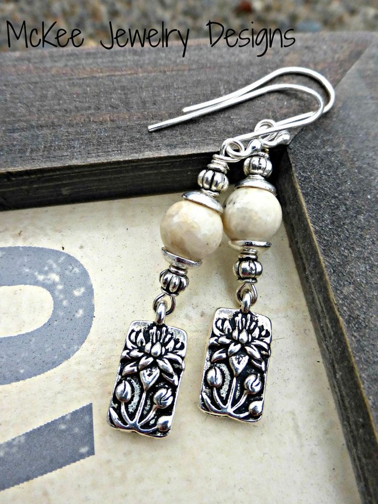 Earrings are lightweight and measure about 2 1/2 inches.With small lotus flower charms, bead caps, silver metal beads and white jasper stone topped with sterling silver ear wires. As with all of my je