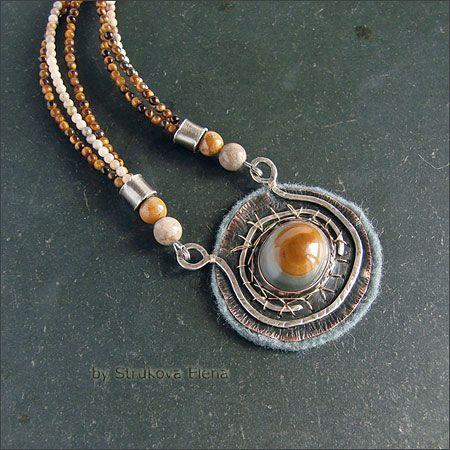 Небольшое ожерелье с агатом и тигровым глазом. Кулон с двухцветным агатом выполнен из патинированного серебра, меди и наполненного золота (gold filled), подложка из фетра серого цвета в тон камню. Кулон крепится на три нити мелких каменных бусинок (агат и тигровый глаз).